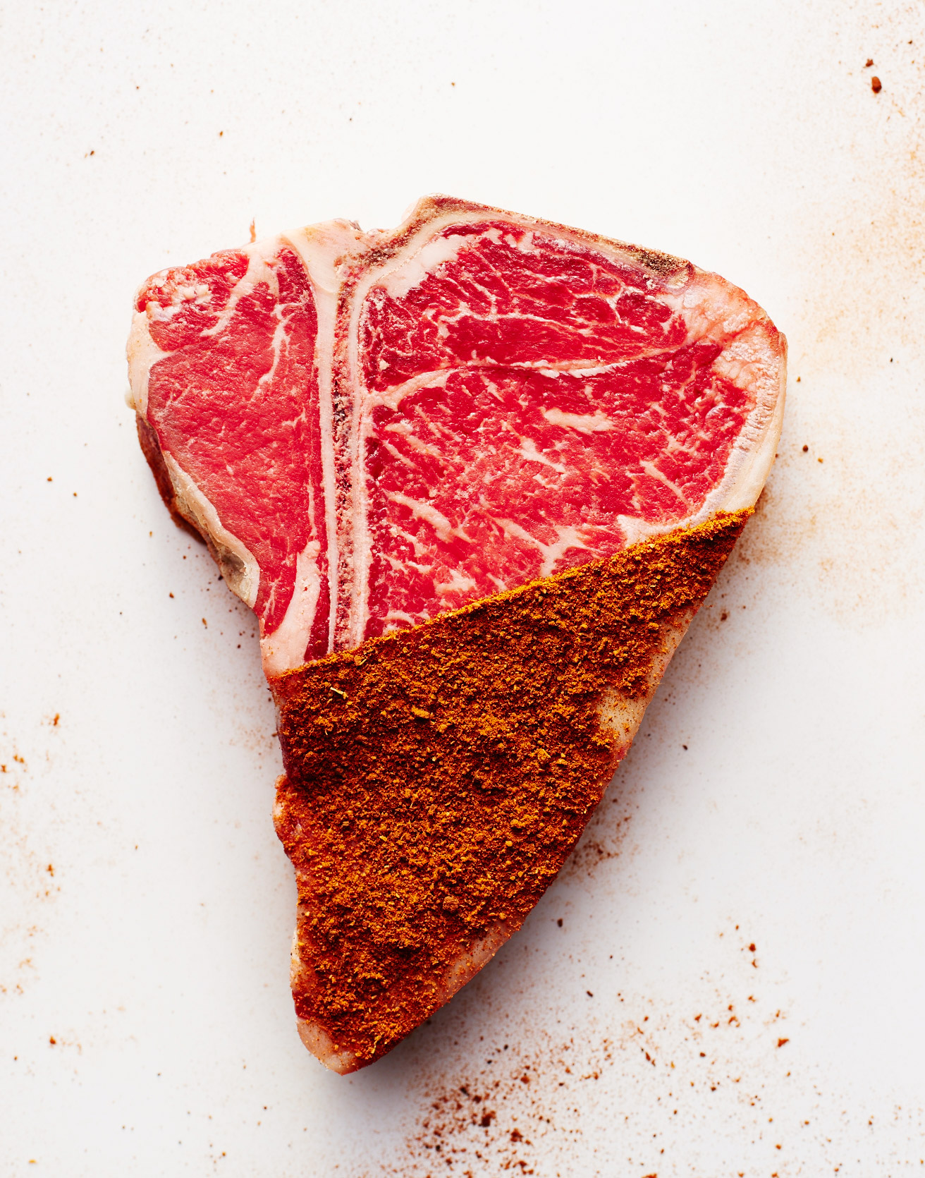 T Bone steak on white with dry rub  by  Ted Cavanaugh