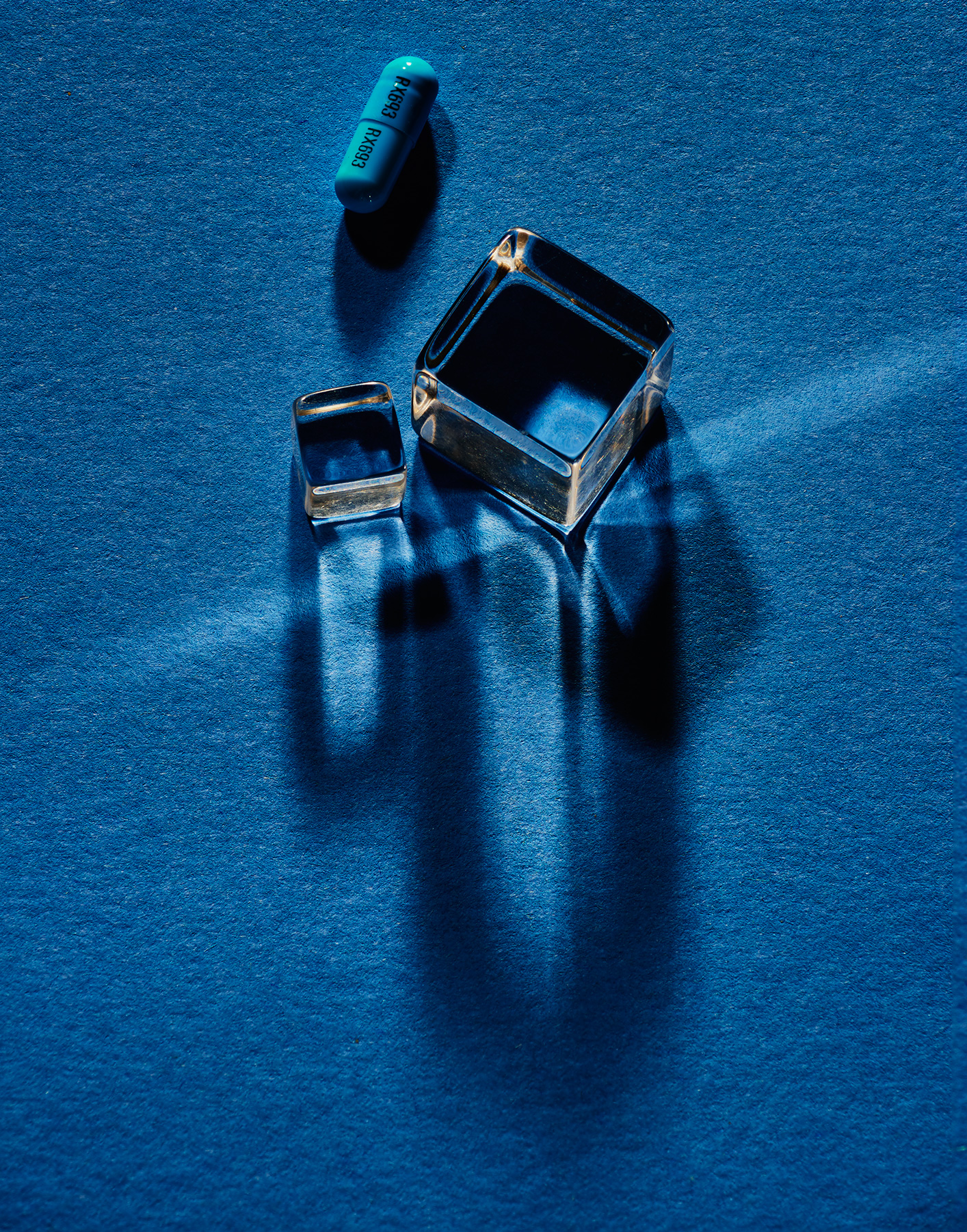 composition of cubes and pills on blue background  by Ted Cavanaugh